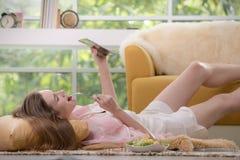 Gezonde jonge vrouw die op de vloer liggen die salade eten en tabletcomputer bekijken stock foto's