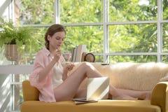 Gezonde jonge vrouw die op een laag liggen die een kom yoghurt houden die ontspannen en comfortabel kijken stock fotografie