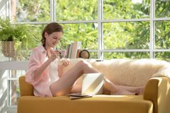 Gezonde jonge vrouw die op een laag liggen die een kom yoghurt houden die ontspannen en comfortabel kijken stock afbeelding