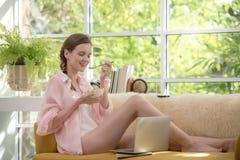 Gezonde jonge vrouw die op een laag liggen die een kom yoghurt houden die ontspannen en comfortabel kijken royalty-vrije stock fotografie