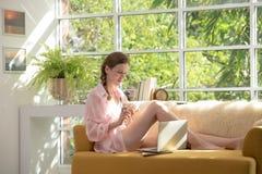 Gezonde jonge vrouw die op een laag liggen die een kom yoghurt houden die ontspannen en comfortabel kijken royalty-vrije stock foto