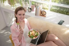 Gezonde jonge vrouw die op een laag liggen die een saladekom houden kijkend ontspannen en comfortabel stock foto