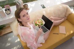 Gezonde jonge vrouw die op een laag liggen die een saladekom houden kijkend ontspannen en comfortabel stock foto's