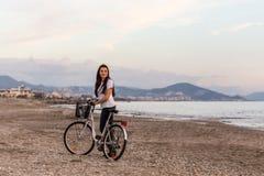 Gezonde levensstijl door het overzees Wijfje met bysicle bij het strand Royalty-vrije Stock Foto