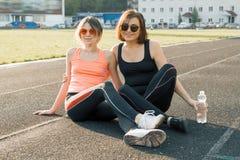 Gezonde levensstijl, gezonde familie Glimlachende geschiktheidsmoeder en tienerdochter die samen bij stadion na het lopen op zonn stock foto