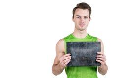 Gezonde Levensstijl Portret van een knappe kerel met een leeg die uithangbord voor het schrijven van, in sportkleding, op een wit Stock Foto's