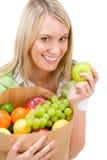 Gezonde levensstijl - vrouw met fruit in document zak Stock Foto's