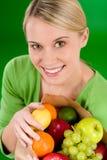 Gezonde levensstijl - vrouw met fruit in document zak Stock Afbeeldingen