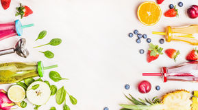 Gezonde levensstijlachtergrond met diverse kleurrijke smoothiedranken in flessen, mixer en ingrediënten op witte houten Stock Foto's