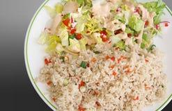 Gezonde maaltijd van wholegrain ongepelde rijst met groenten en een verse die tuinsalade met een romige vulling wordt bedekt stock fotografie
