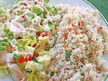 Gezonde maaltijd van wholegrain ongepelde rijst met groenten en een verse die tuinsalade met een romige vulling wordt bedekt stock foto's