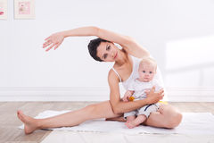 Gezonde moeder en baby die gymnastiek maken royalty-vrije stock afbeelding