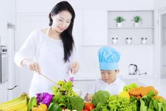Gezonde moeder en zoon die salade maken stock fotografie