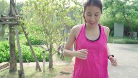 Gezonde mooie jonge Aziatische agentvrouw in sporten die het lopen kleden en op straat in stedelijk stadspark aanstoten stock video