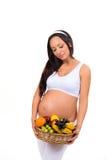 Gezonde mooie zwangere donkerbruine vrouw met een mand fruit Royalty-vrije Stock Fotografie