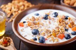 Gezonde ontbijt Verse granola, muesli met bessen, honing en melk op een houten kom Houten achtergrond Stock Foto's