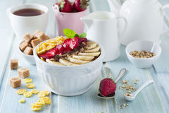 Gezonde ontbijtcornflakes, banaan, aardbei, amandel, chocolade en yoghurt in een ceramische kom Stock Fotografie