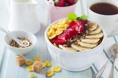 Gezonde ontbijtcornflakes, banaan, aardbei, amandel, chocolade en yoghurt in een ceramische kom Royalty-vrije Stock Foto