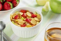 Gezonde ontbijtcornflakes en aardbeien met melk en appelsap stock foto