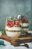 Gezonde ontbijtglazen met yougurt, granola en sinaasappel gelaagd parfait stock foto