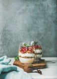 Gezonde ontbijtglazen met yougurt, granola, sinaasappel gelaagd parfait, munt stock foto's