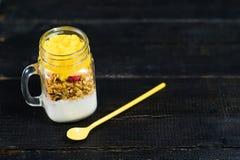 Gezonde ontbijtmuesli en yoghurt met mango smoothie in de kruiken van de glasmetselaar stock fotografie