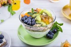 Gezonde ontbijtyoghurt met chiazaden, graanstootkussens, kiwi, bosbessen en physalis op een witte achtergrond royalty-vrije stock foto