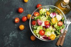 Gezonde plantaardige salade van verse tomaat, komkommer, ui, spinazie, sla en pompoenzaden in kom Dieetmenu Hoogste mening met co stock afbeelding
