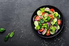 Gezonde plantaardige salade van verse tomaat, komkommer, ui, spinazie, sla en sesam op plaat Dieetmenu stock afbeelding