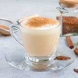 Gezonde rooibos rode die thee latte met kaneel, in een glaskop en ingrediënten op achtergrond, vierkant formaat wordt bedekt Royalty-vrije Stock Afbeeldingen