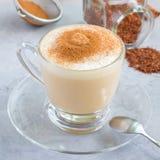 Gezonde rooibos rode die thee latte met kaneel, in een glaskop en ingrediënten op achtergrond, vierkant wordt bedekt Stock Foto's