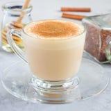 Gezonde rooibos rode die thee latte met kaneel, in glaskop en ingrediënten op achtergrond, vierkant formaat wordt bedekt Stock Afbeeldingen