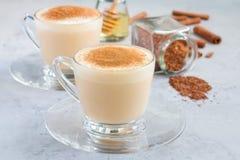 Gezonde rooibos rode thee latte die met kaneel, ingrediënten op achtergrond wordt bedekt Royalty-vrije Stock Foto's