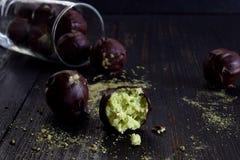 Gezonde ruwe energiebeten met kokosnoot, avocado en theematcha De truffels van de veganistchocolade op donkere houten achtergrond Stock Afbeeldingen
