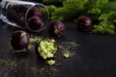 Gezonde ruwe energiebeten met kokosnoot, avocado en theematcha De truffels van de veganistchocolade op donkere houten achtergrond Stock Foto