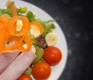 Gezonde salade van ham, tomaten, wortelen, bananen, raket, sla groene olijven en druiven Stock Fotografie