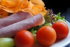 Gezonde salade van ham, tomaten, wortelen, bananen, raket, sla groene olijven en druiven Royalty-vrije Stock Afbeeldingen