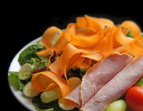 Gezonde salade van ham, tomaten, wortelen, enz. op schone zwarte achtergrond Stock Afbeeldingen