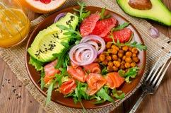 Gezonde saladekom met zalm, grapefruit, kruidige kekers, avo stock foto