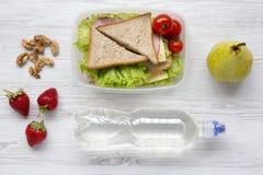 Gezonde schoolmaaltijddoos met verse organische groentensandwiches, okkernoten, fles water en vruchten op witte houten achtergron royalty-vrije stock foto's