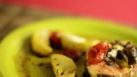 Gezonde schotel, geroosterde oncorhynchusketa met groenten in de groene plaat HD videoomwenteling stock video