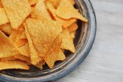 Gezonde Snack Nachios in Blauwe Plaat Sluit omhoog voedsel Oranje Nachos met kruiden Grijze rustieke Lijst stock afbeelding