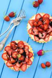 Gezonde snoepjes Verse sappige aardbeien op tartlets met room Stock Foto