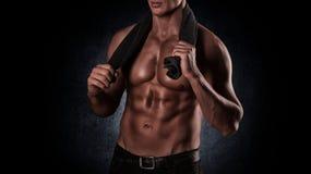 Gezonde spier jonge mens na een training op donkere achtergrond stock afbeeldingen