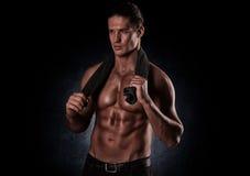 Gezonde spier jonge mens na een training op donkere achtergrond stock foto's