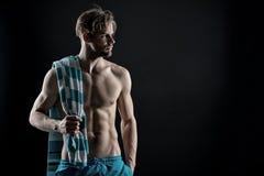 Gezonde spier jonge mens na training op donkere achtergrond, wijnoogst Royalty-vrije Stock Fotografie