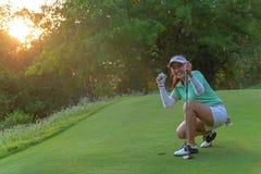 Gezonde sport Golfingsspel De Aziatische actie van de vrouwengolfspeler om na lange het zetten golfbal op het groene golf, in ope royalty-vrije stock foto's