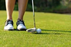 Gezonde sport Sluit nadruk van de Golfspeler omhoog de Aziatische sportieve vrouw zettend golfbal op het groene golf op avondtijd stock afbeeldingen