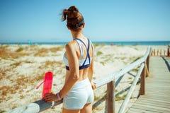 Gezonde sportenvrouw met fles water op zeekust stock fotografie