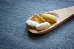 Gezonde supplementen op houten lepel royalty-vrije stock afbeelding